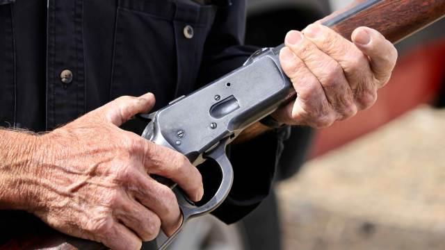 Deko Winchester Gewehr Unterhebelrepetierer in der Hand eines Cowboys